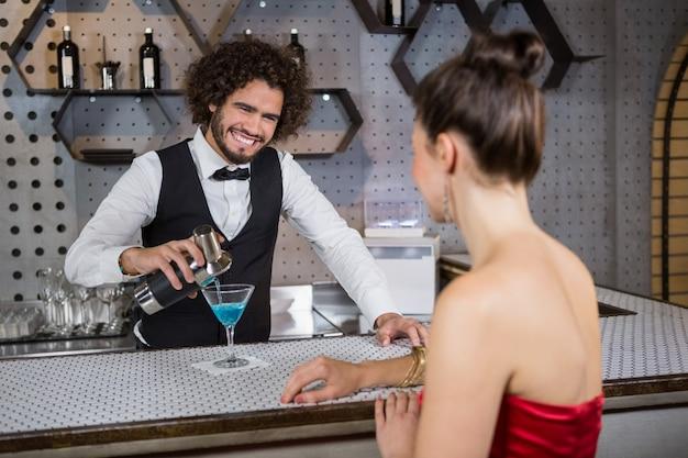 Garçom, derramando coquetel no copo da mulher no balcão de bar
