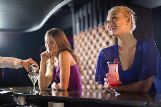 Garçom, derramando um coquetel no copo de mulher no balcão de bar