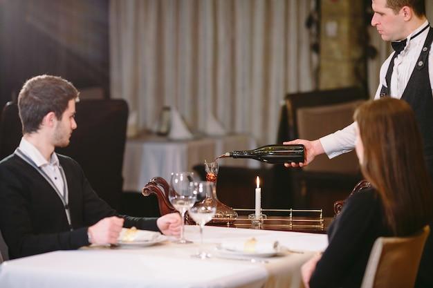 Garçom, derramando vinho tinto em um copo em uma mesa de restaurante