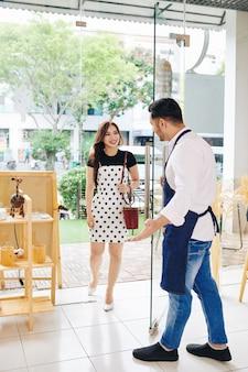 Garçom do café abrindo a porta de entrada de vidro para uma linda cliente e a convidando para entrar