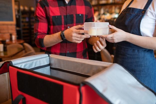Garçom do café passando o recipiente de plástico com o pedido do cliente para o mensageiro sobre a grande sacola vermelha aberta enquanto faz a embalagem da comida