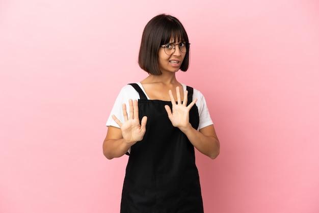 Garçom do restaurante sobre fundo rosa isolado nervoso esticando as mãos para a frente