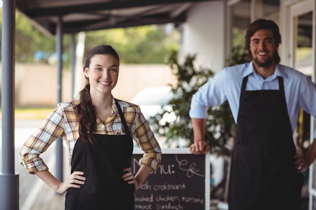 Garçom e garçonete em pé com cardápio fora do café