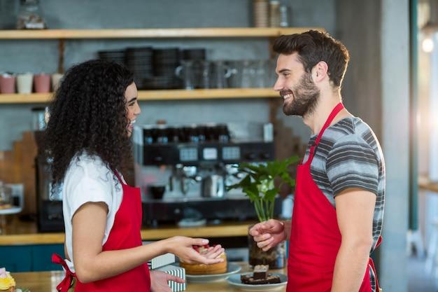 Garçom e garçonete interagindo uns com os outros no café