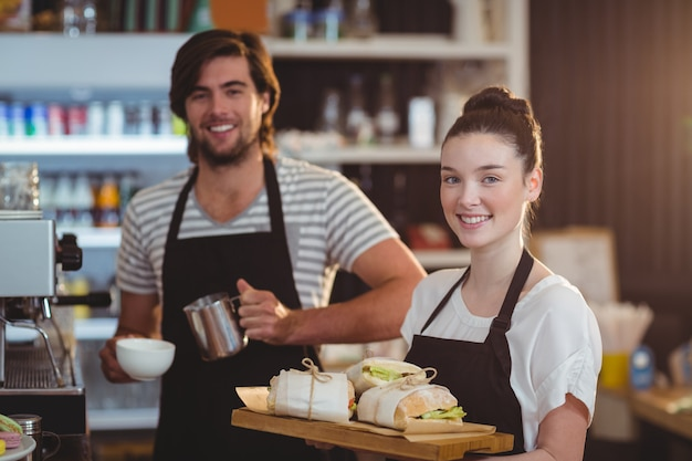 Garçom e garçonete, segurando o prato de jarro de refeição e café