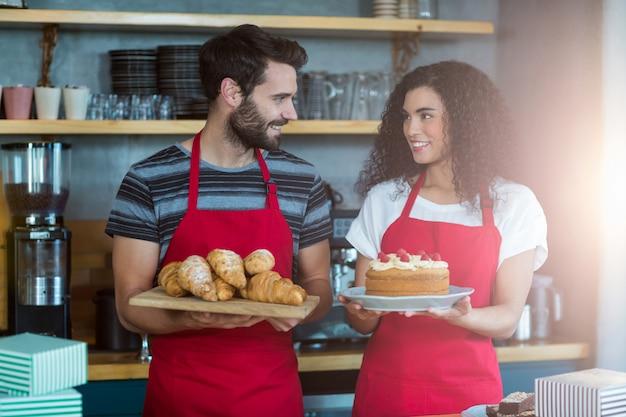 Garçom e garçonete segurando uma bandeja de croissants e bolo