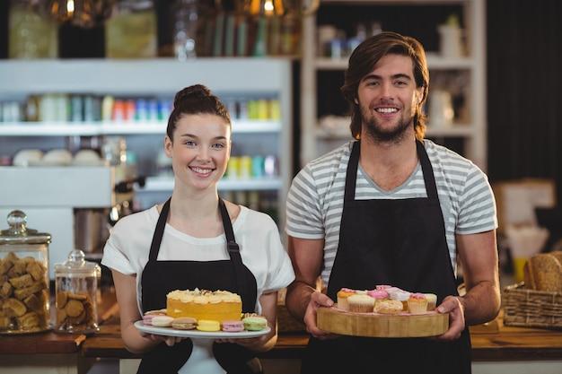 Garçom e garçonete segurando uma bandeja de cupcakes