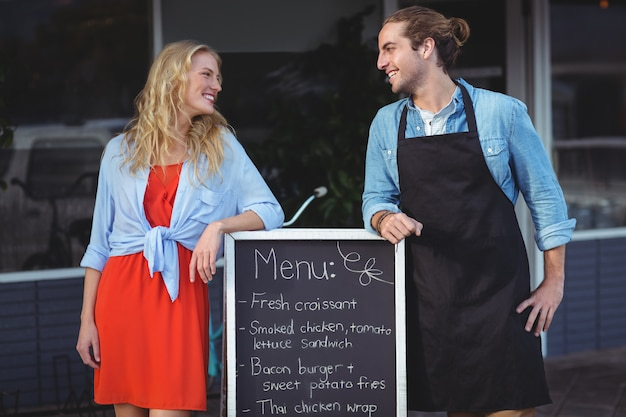 Garçom e mulher em pé com cardápio fora do café