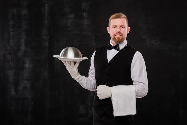 Garçom elegante e feliz em um restaurante elegante segurando uma toalha branca e um cloche com comida em pé contra um fundo preto