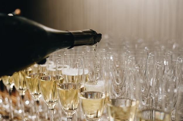 Garçom está servindo champanhe em taças, champanhe