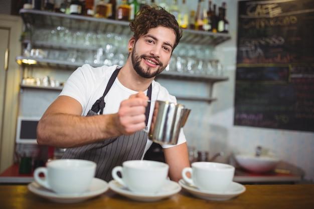 Garçom fazendo chávena de café no balcão no café