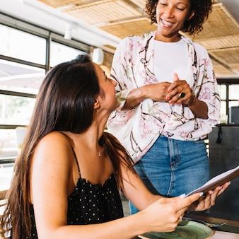 Garçom feminino recebendo ordens do cliente jovem no restaurante