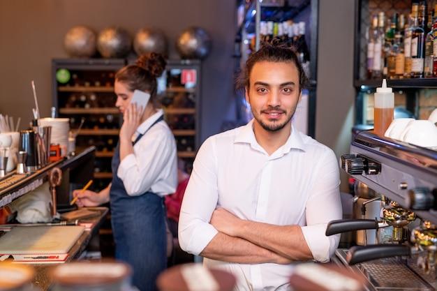 Garçom jovem bonito de camisa branca cruzando os braços ao lado da máquina de café no fundo de um colega ligando