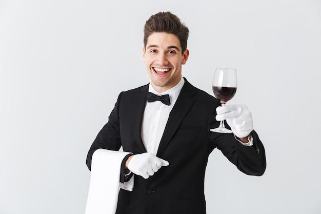 Garçom jovem e bonito de smoking segurando uma taça de vinho tinto isolada na parede cinza