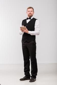 Garçom jovem e elegante com bloco de notas e caneta anotando o pedido de um dos clientes do restaurante isolado