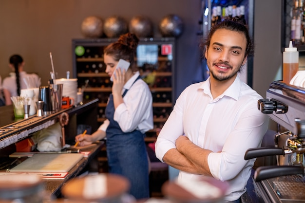 Garçom jovem e feliz com braços cruzados em uma camisa branca em frente à câmera no fundo de um colega falando com o cliente ao telefone