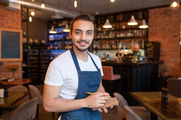Garçom jovem e feliz com camiseta branca e avental azul escuro olhando para você com um sorriso largo e escrevendo seu pedido no restaurante