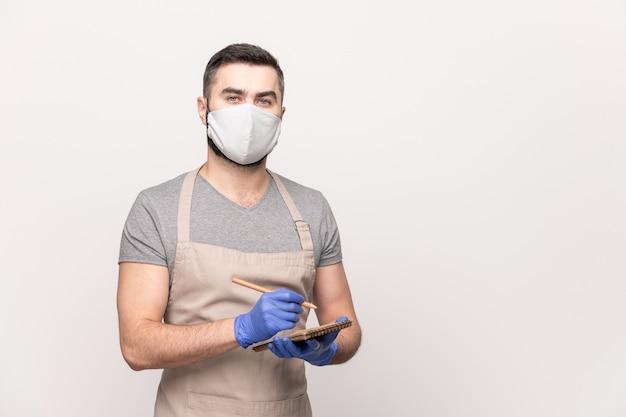 Garçom jovem e sério de avental, máscara protetora e luvas, escrevendo seu pedido no bloco de notas enquanto trabalha em um café ou restaurante