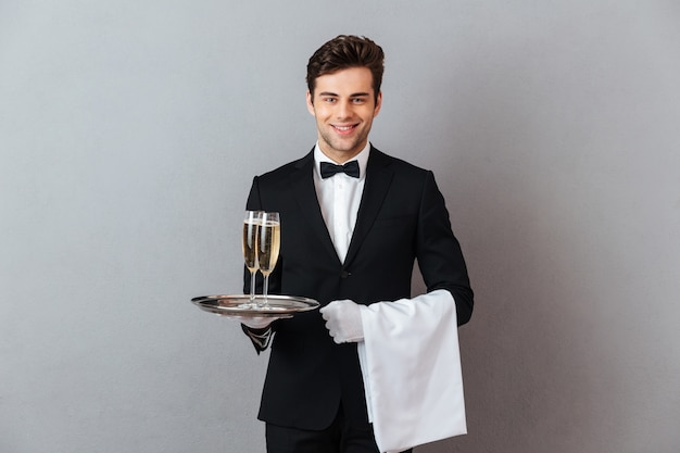 Garçom jovem feliz, segurando a taça de champanhe e toalha.