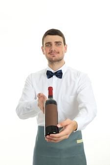 Garçom jovem segura uma garrafa de vinho, isolada no fundo branco.