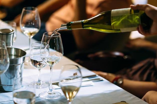Garçom mão derramando vinho em um copo servido mesa