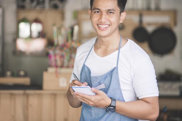 Garçom masculino asiático em ordem de escrita do avental