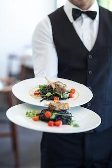 Garçom, mostrando um prato