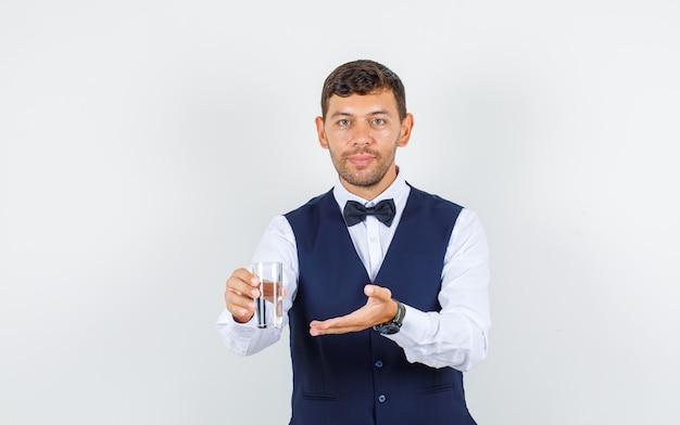 Garçom oferecendo um copo de água na camisa, colete e olhando alegre, vista frontal.