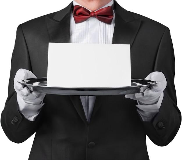 Garçom ou mordomo vestindo um smoking segurando um cartão em uma bandeja de prata na frente de seu torso.