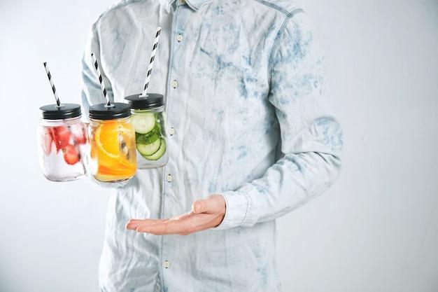 Garçom segura três refrescos gelados de morango, laranja, limão, hortelã, pepino, gelo e água com gás em potes rústicos com canudinhos dentro