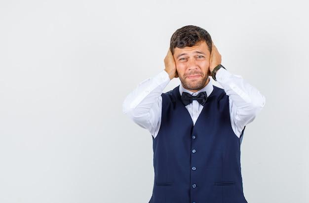 Garçom segurando as mãos nas orelhas na camisa, colete e parecendo irritado, vista frontal.