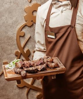 Garçom, segurando, miudezas cordeiro, decorado, com, sumagre, e, cebola, servido, ligado, tábua madeira