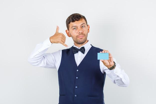 Garçom segurando o cartão com o gesto do telefone na camisa, colete e olhando útil, vista frontal.