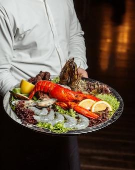 Garçom, segurando, prato frutos do mar, com, lagosta, rei, camarões, e, mexilhões