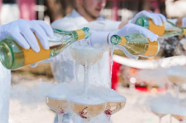 Garçom serve champanhe de 2 garrafas em taças de cristal com gelo seco e fumaça branca de perto