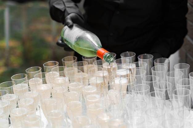 Garçom serve champanhe na taça de vinho