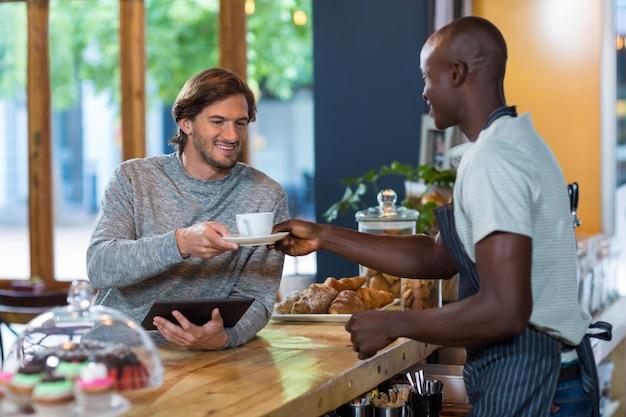 Garçom servindo café ao cliente masculino
