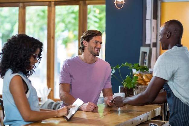 Garçom, servindo café, homem, enquanto, mulher, usando, tablete digital, contador
