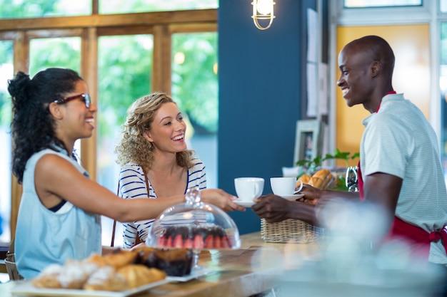 Garçom servindo café para clientes do sexo feminino