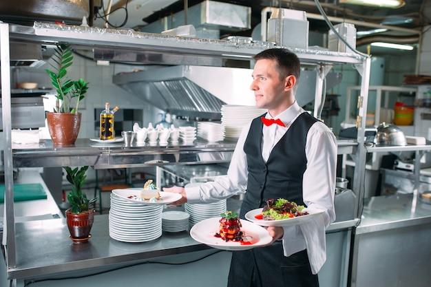 Garçom, servindo em movimento de plantão no restaurante. o garçom leva pratos