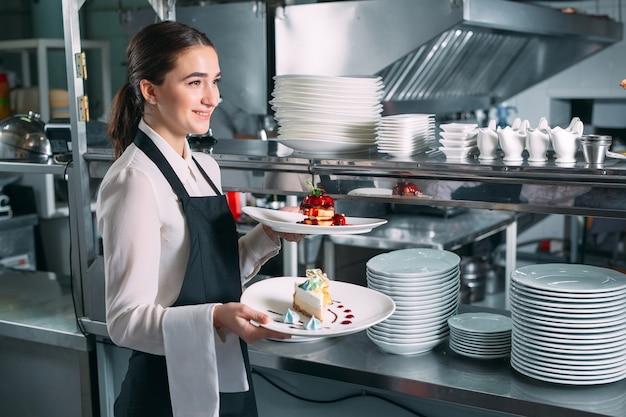 Garçom, servindo em movimento de plantão no restaurante. o garçom leva pratos.