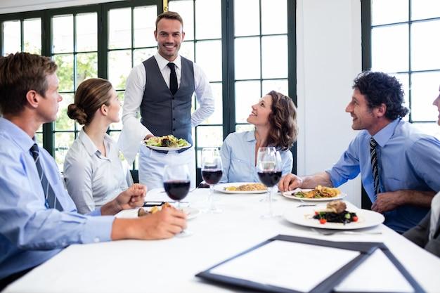 Garçom servindo salada para pessoas de negócios