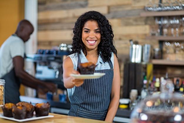 Garçom, servindo um copo de bolo no balcão