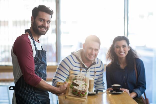 Garçom, servindo um prato de sanduíche ao cliente no café