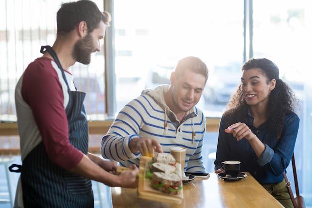Garçom, servindo um prato de sanduíche ao cliente