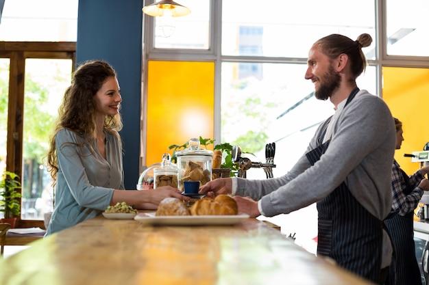 Garçom, servindo uma xícara de café para o cliente no balcão