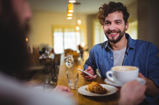 Garçom servindo uma xícara de café para o cliente