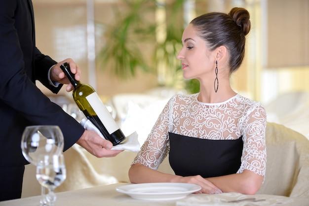Garçom servir vinho para uma jovem mulher elegante