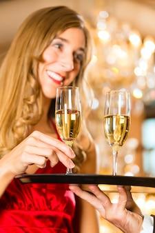 Garçom serviu taças de champanhe em uma bandeja em um restaurante requintado e a mulher toma um copo, um grande lustre está