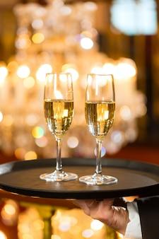 Garçom serviu taças de champanhe em uma bandeja em um restaurante requintado, um grande lustre está